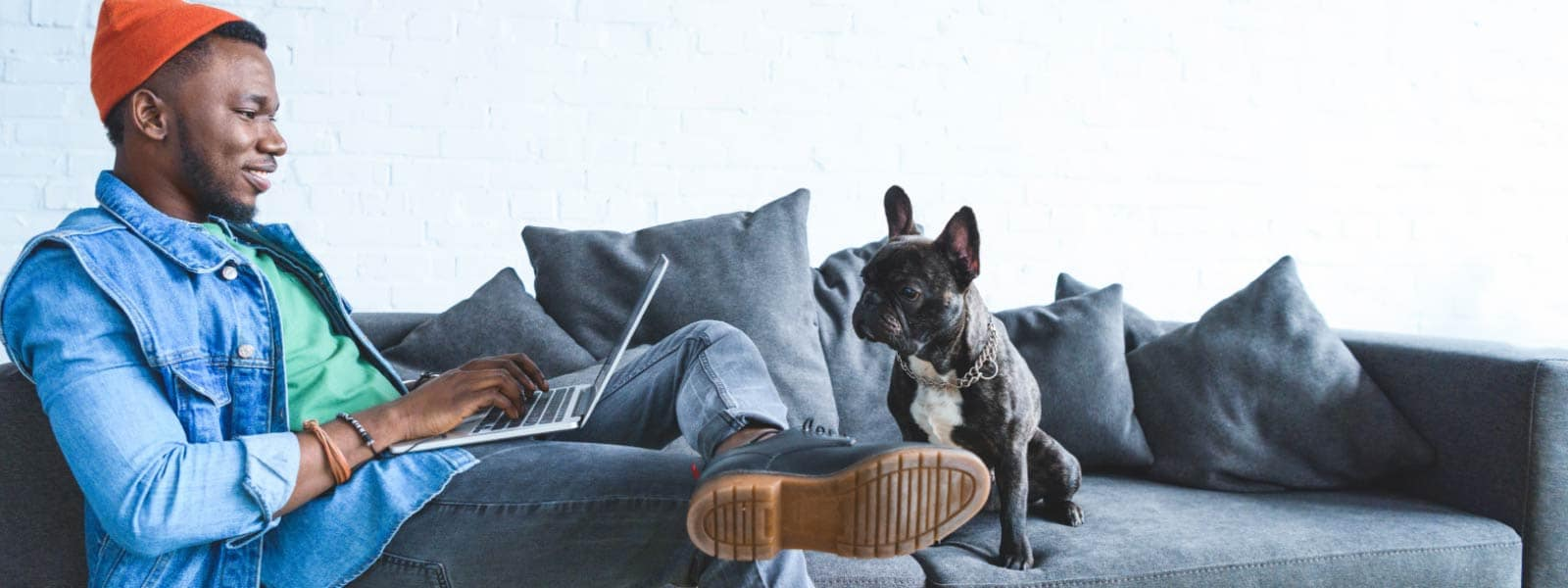 a black man in a denim button-up shirt with a red cap sits on a grey couch, with his laptop in his lap and a black French bulldog beside him, indicating he is browsing online and others may be able to view his IP address